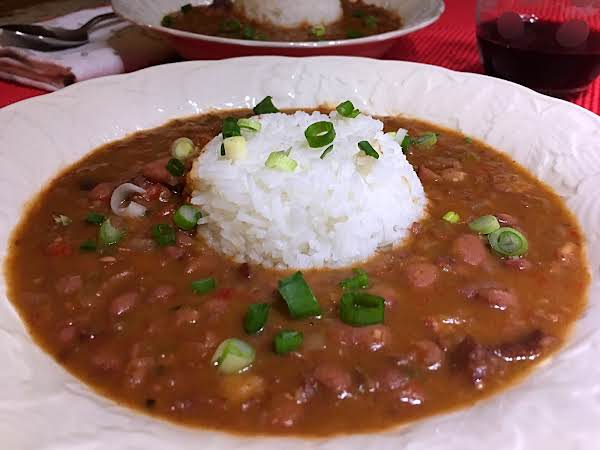 Beans In A Bowl With Rice In The Middle And Garnished With Chopped Green Onions With Another Bowl Of Beans And A Glass Of Red Wine On A Red Table Mat.