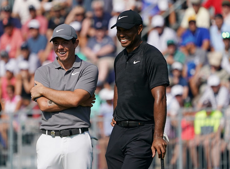 Rory McIlroy (left) laughs with Tiger Woods (right) on the 18th green during the continuation of the second round of the PGA Championship golf tournament at Bellerive Country Club on August 11, 2018 in Saint Louis.