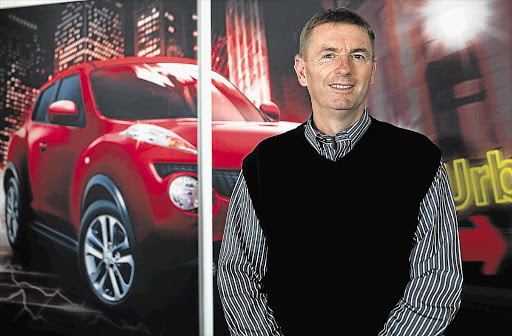 Car dealer Mark White with a poster of a funky Nissan Juke in the background