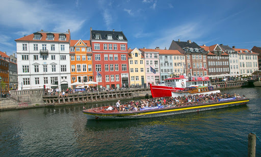Visitors on a canal cruise pass through the Nyhavn neighborhood of Copenhagen.