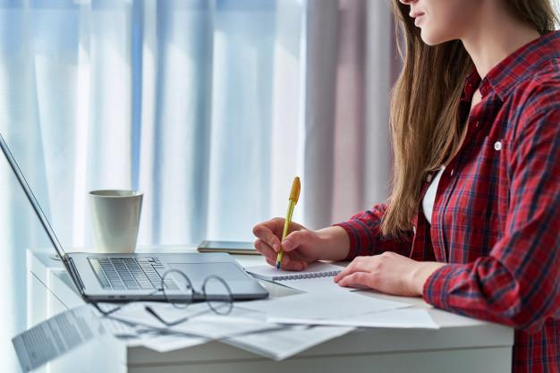 Woman working remotely on laptop and writing down important data information in notebook. student during distance education and online courses learning at home Premium Photo