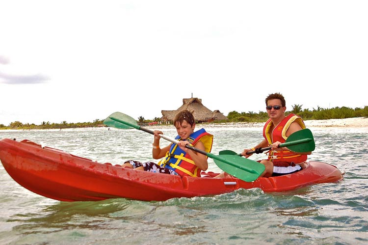 A father and son kayaks during a cruise.