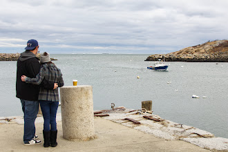 Photo: Young couple standing on pier watching the boats come on winter afternoon at Rockport MA  Attribution, Noncommercial, No Derivative Works