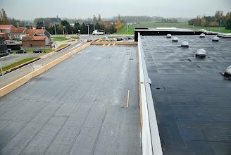 Photo: 12-11-2012 © ervanofoto Het dak van het magazijn (rechts) en dat van onze burelen (links). Op het dak van de burelen ligt slechts een eerste waterdichtingslaag in roofing. De verdere afwerking omvat twee lagen van elk 16 cm isolatie en een laag rubberen dakdichting (EPDM). Dit zal over een één á twee weken gebeuren.
