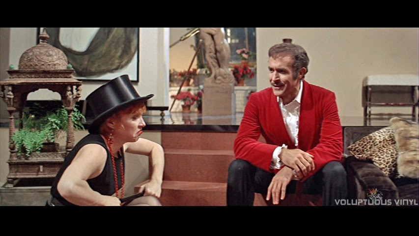 Shirley MacLaine (Charity) sits with a frown on her face, and a black top hat, talking to Vittorio.
