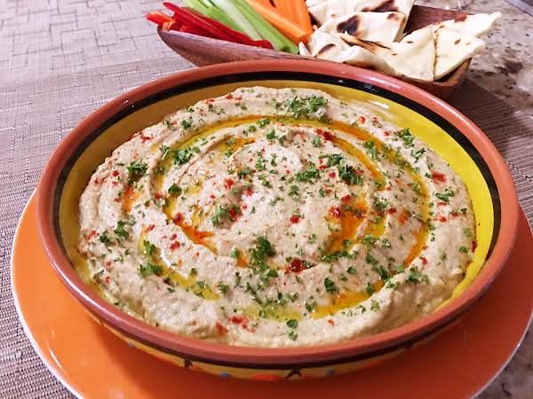 Baba Ghanoush In A Serving Dish Sitting On A White/orange Plate With Crudites In The Background.