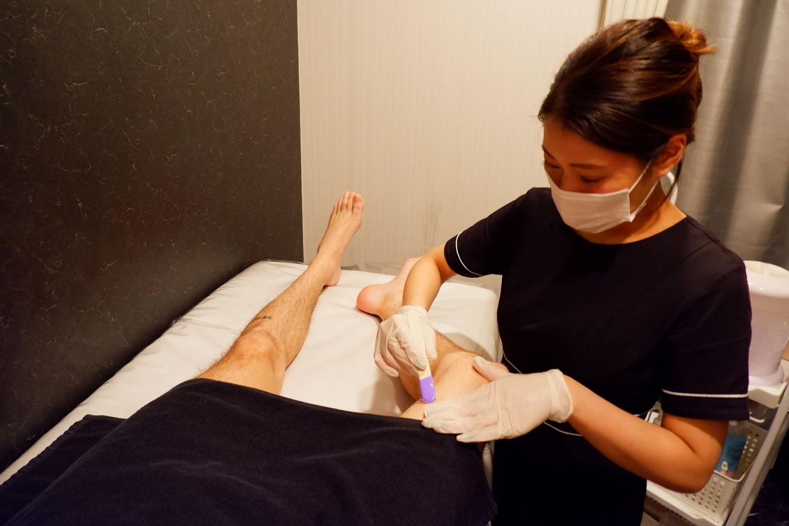 男性の脚のブラジリアンワックス脱毛の施術