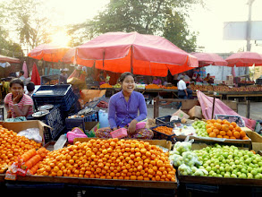 "Photo: This happy lady is selling small tangerines and green plums.  This is in their version of ""Chinatown""."