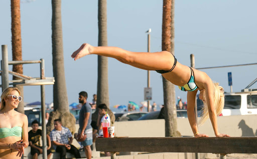 A young woman discounts a balance beam at Muscle Beach in Venice, California.