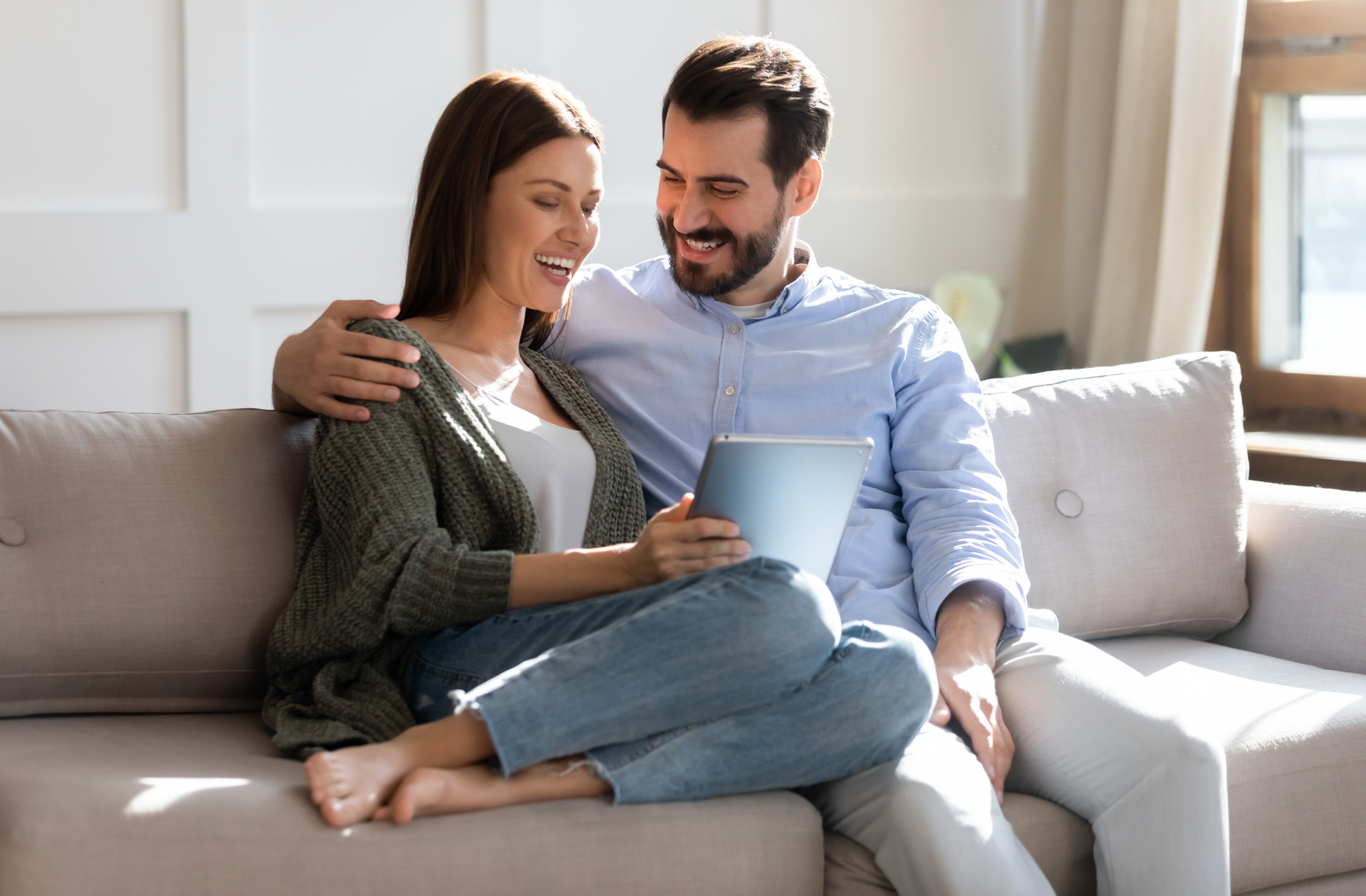 Relieved couple sitting on the couch reading an email telling them they've been approved for a payday advance.
