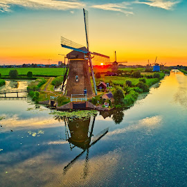 windmills at sunset in Kinderdijk, The Netherlands by Vasilis Ververidis - Buildings & Architecture Other Exteriors ( kinderdijk, rural, scenic, aerial, scene, spring, cloud, dutch, view, golden, farm, sky, environmental, reflection, holland, old, windmill, european, netherlands, heritage, history, water, drone, mill, traditional, field, vintage, idyllic, wind, sunrise, yellow, destination, scenery, sun, gold, agriculture, rustic, ecology, architecture, picturesque, nature, countryside, retro, environment, blue, culture, sunset, river, travel, landscape )