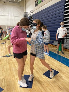 two students standing on tiles in the gym, one is blindfolded