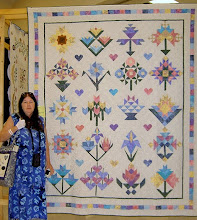 "Photo: Mary with ""A Quilter's Garden"".Pattern by Lynette Jensen of Thimbleberries came with 12 blocks, we increased it to 20 - found some blocks on the internet and designed some ourselves."