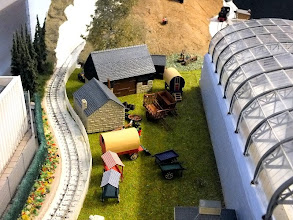 Photo: 111 Horsedrawn wagons and 2 traditional gypsy caravans spotted behind the station of the Hampshire 'Og provide something of a Paulton's Park feeling to this part of Derek Johnson's unusual 009 layout .