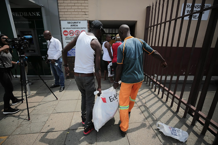 Customers queue to return meat to the Enterprise factory store in Germiston, east of Johannesburg, on March 5 2018.