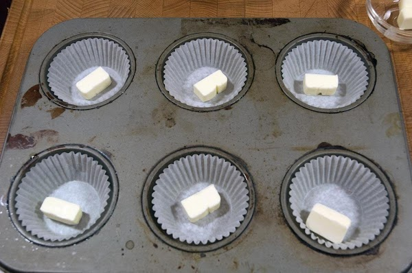 Add 1/2 tablespoon of butter to the bottom of the muffin tins.