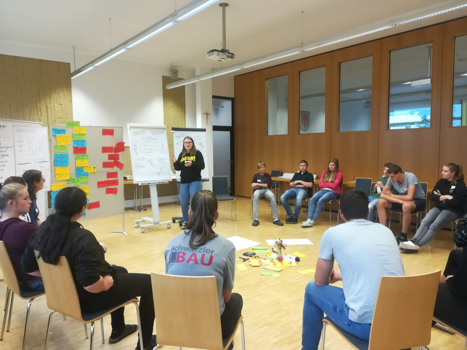 The image is of a classroom with a group of young people sitting in a semi-circle. A person with long hair in a black long sleeve shirt and jeans stands and gestures towards a white board next to her.