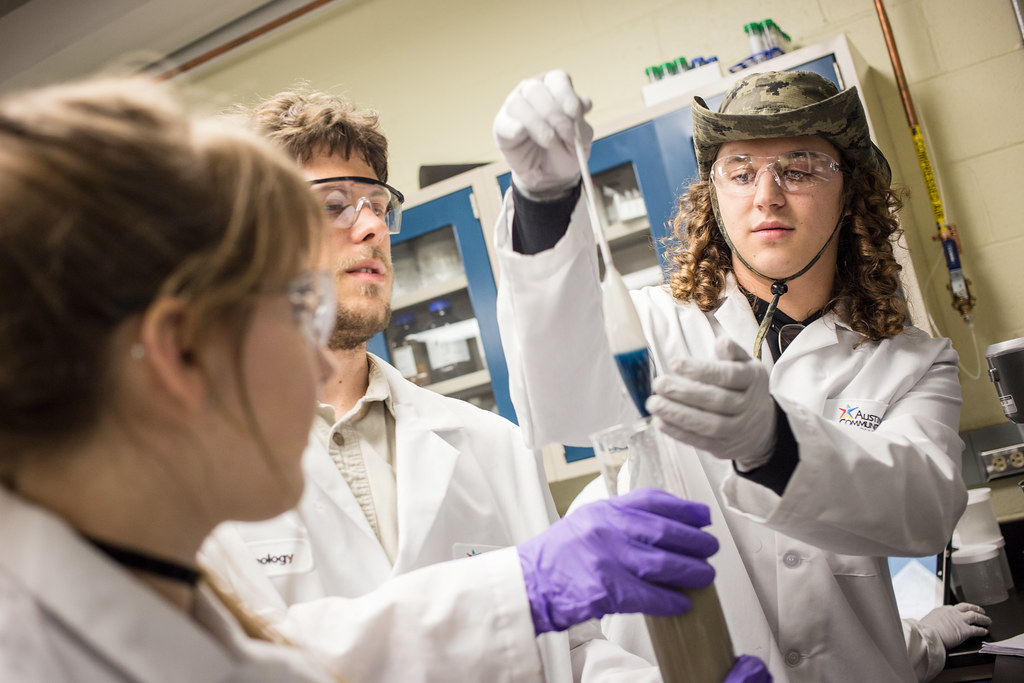Three high school students wear gloves and eye protection as they work on research together in a laboratory.
