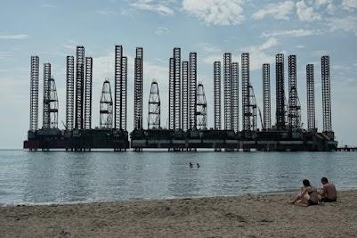 Nur wenige Meter vom Strand entfernt stehen alte Bohrinseln im Kaspischen Meer.
