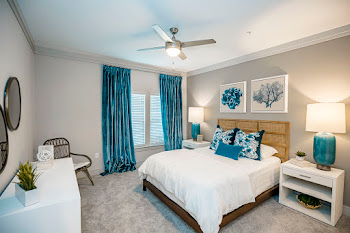 B1 model bedroom with neutral carpet and ceiling fan and bedroom furniture