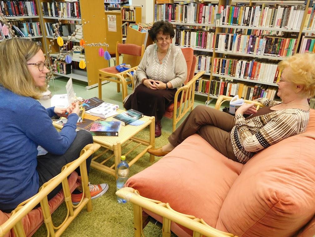 Olvasó és beszélgető felnőttek a könyvtárban