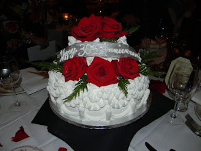 Photo: 2-tier stacked cake w/Lisa's traditional border (doubled). Featuring fresh red roses & winter greens. Writing over silver French ribbon bow topper. Fresh roses & greens provided by customer.