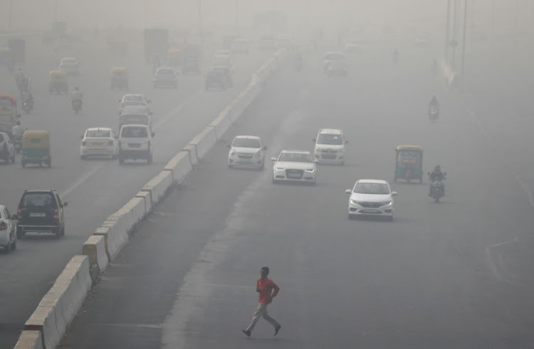 A man runs across an expressway cloaked in smog near Delhi, India November 13, 2017.