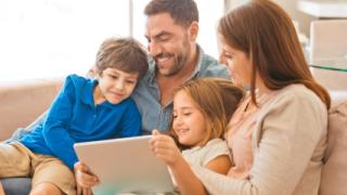 una familia de cuatro miembros mirando un tablet juntos