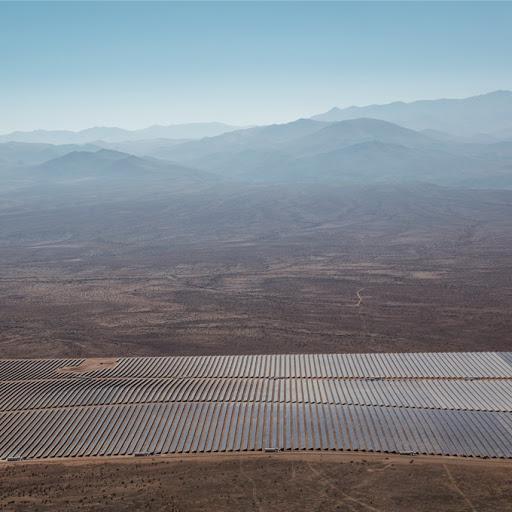 Solarpark in der Wüste mit Bergen im Hintergrund