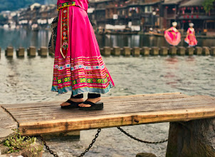 Photo: A girl crosses an ancient bridge in the small town of Feng Huang, China.