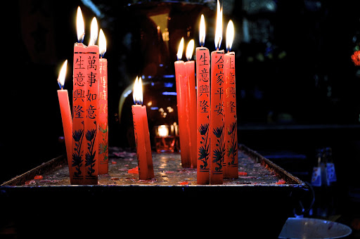 Red candles flicker in a beautiful Buddhist temple in Hanoi, Vietnam.