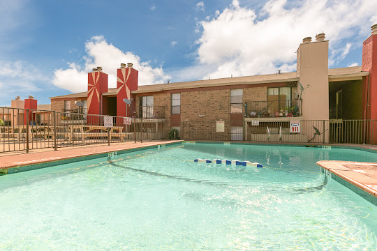 L-shaped pool with a view of two-story apartment building with brown brick exterior and chimneys
