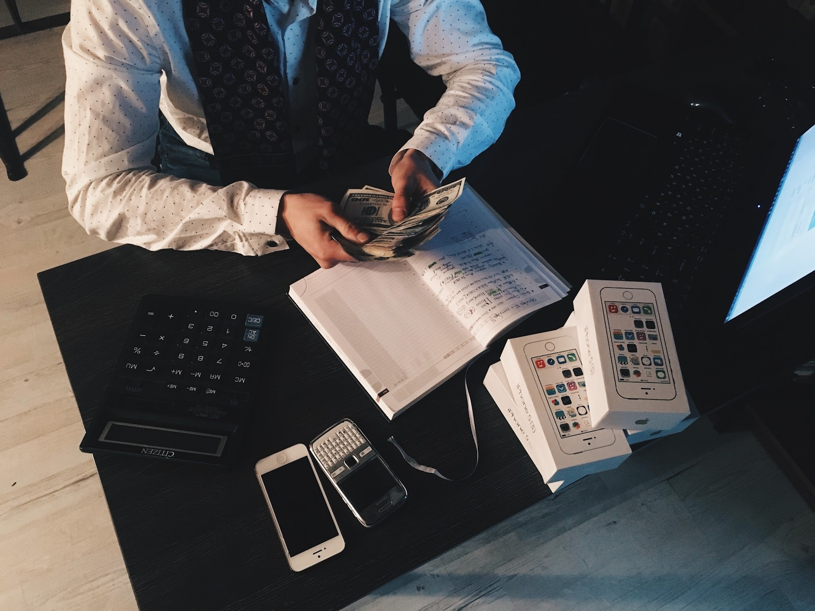 person-counting-money-with-smartphones-in-front-on-desk- small business on a budget tips