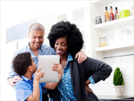 A young boy shows his parents an image on a digital tablet