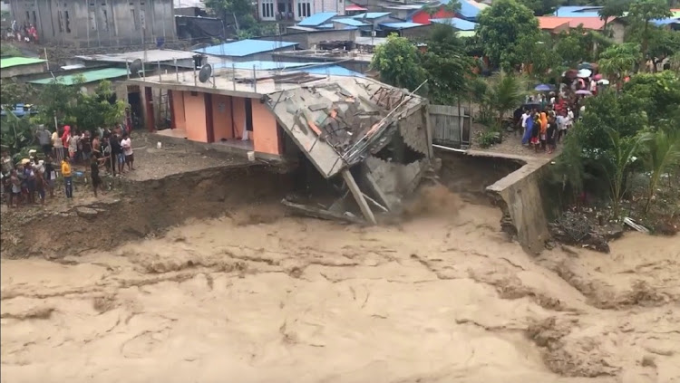 A house collapses after its foundations were washed away as the Comoro River is flooded in Dili, East Timor April 4, 2021, in this still image obtained from a social media video.