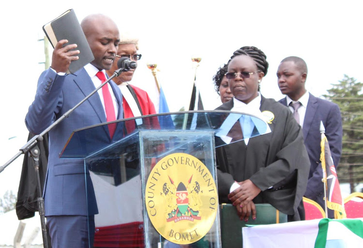 Incoming Bomet Governor Hillary Barchok being sworn in to office by Kericho high Court Judge George Dulu at Bomet Stadium on August 8, 2019.