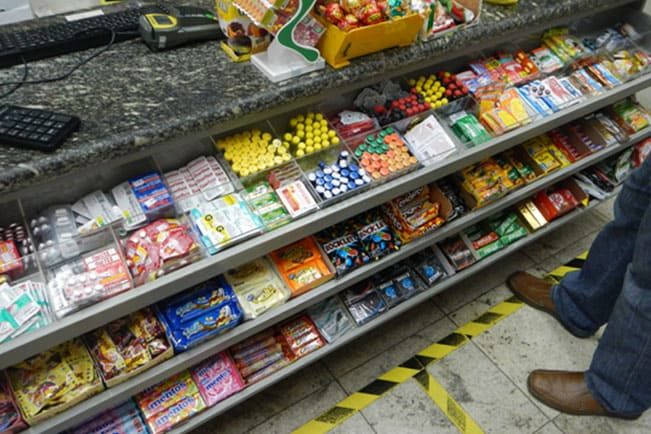 A imagem mostra um checkout de farmácia com produtos alimentícios e MIPs.