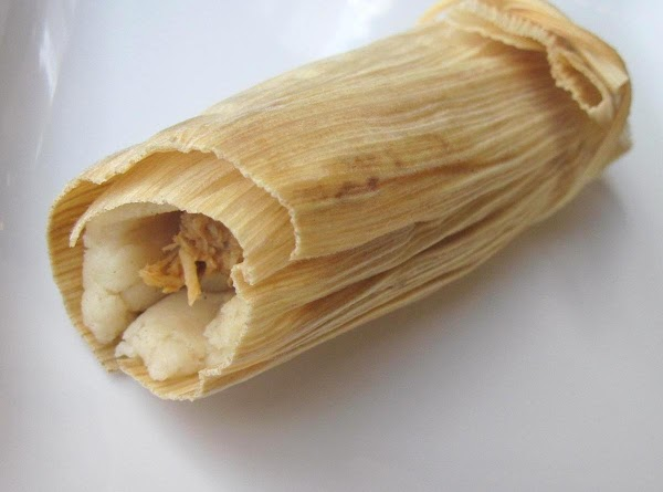 Carefully roll the tamale, starting with the side covered with the Masa Dough. Turn...