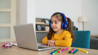 young girl sitting in front of laptop with headphones on
