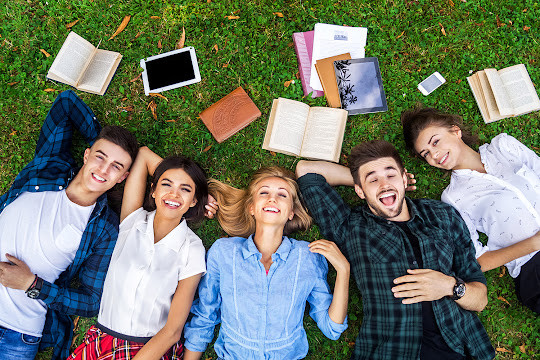 College students laying in grass surrounded by books