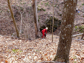 Photo: Trish chilling out on a downed tree & Doug coming up the hill from the entrance