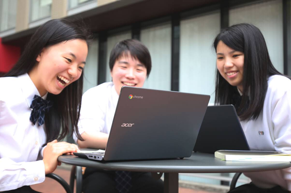 三人の生徒が Chromebook を見てます