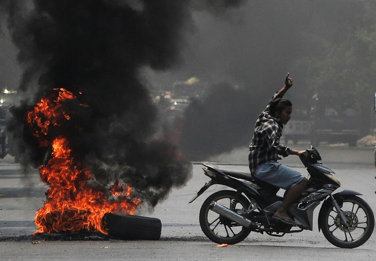 A man flashes the three-finger salute as he passes burning tires during a protest against the military coup, in Mandalay, Myanmar on April 1, 2021. Picture: REUTERS