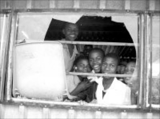 DEPLORABLE: Pupils at Sikhulisile Primaruy School look out through a broken classroom window. Pic. McKeed Kotlolo. © Sowetan.