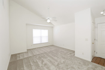 Living room with light carpet and white walls