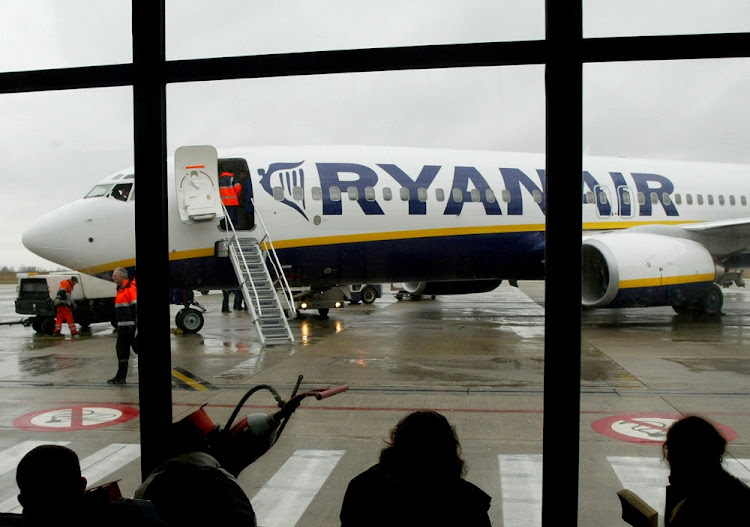 Travellers wait in front of a passenger jet belonging to Irish discount airline Ryanair at Charleroi airport in southern Belgium. Picture: REUTERS