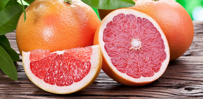 A whole grapefruit with leaves along with a sliced grapefruit on a table.
