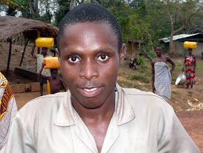 Photo: atteint de paralysie des 2 membres inférieurs, nous lui avons apporté un fauteuil roulant, l'avons fait rééduquer et appareiller chez Emile, scolarisé au village, puis au collège de Bopa où il se rend avec un tricycle