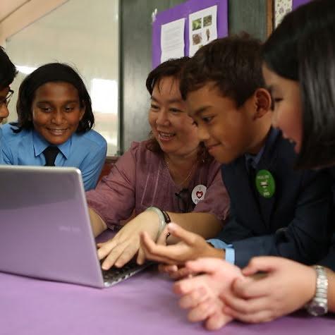 """Eine Gruppe von Schülern arbeitet an Laptops. Auf einem Schild steht """"Machine Learning""""."""