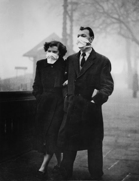 Photo: A couple wearing masks to protect them from the smog in Blackfriars, London, 18th November 1954. (Photo by Monty Fresco/Topical Press Agency/Getty Images)